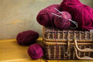 cestas-mimbre-cesta-vendimia-ovillos-lana-roja-agujas-mesa-madera_76014-86